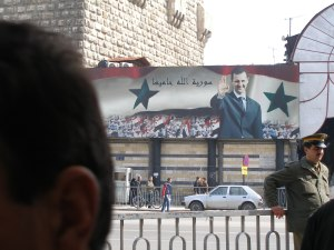 Unintended irony in the caption beside Bashar: 'God is Syria's Protector'