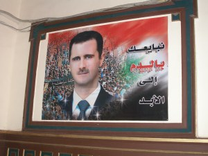 Prophetic 2007 poster of Bashar in Damascus' Hijaz Railway with the caption: 'We pledge allegiance to you with blood forever.' Blood drips from the words 'with blood'.[DD]