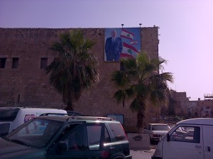 Banner of Rafiq al-Hariri adorns the Khan al-Franj, caravanserai of the Franks, restored by Rafiq al-Hariri to be a craft centre and tourist office, now empty [DD, 2014]